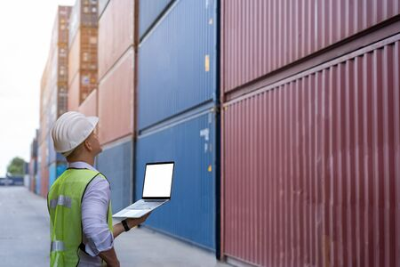 inspection engineer wear helmet and uses laptop computer to check the accuracy of the container before exporting or receiving the product.Prepare for importing or exporting products in container yard.