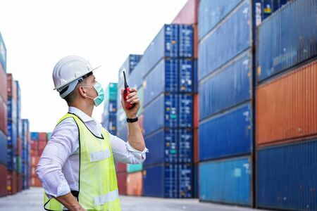 new normal concept.inspector engineer or project engineer wear helmet and mask and use walkie talkie to contact the factory team or container yard.Remote execution to prevent Coronavirus infection