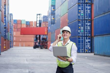 new normal concept, inspector engineer using laptop and walkie talkie for remote commanding in the factory or Container yard or check the correctness of the container before importing or exporting Stockfoto