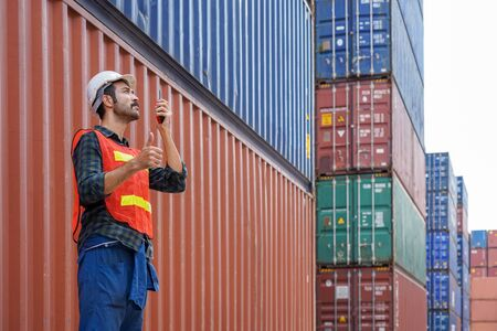 new normal concept.inspector engineer or project engineer wear helmet and use walkie talkie to contact the factory team or container yard.Remote execution to prevent Coronavirus infection