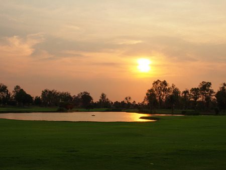 The evening sunset on the large yard with the reflection of the sunlight on the little lake,