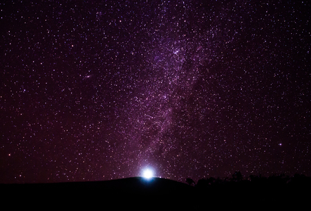 genesis: One spotlight at the tip of the hill with the milkyway galaxy and lots of stars above in Chiangmai, Thailand. Stock Photo