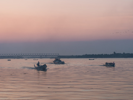 The three boats are gliding back home in the evening vanilla sky.