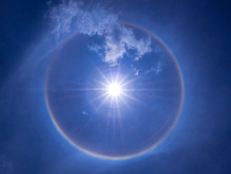 cirrus: The phenomenon of sunlight refract to the moisture in the atmosphere, the sun halo over the bright clear sky and little cloud. Stock Photo