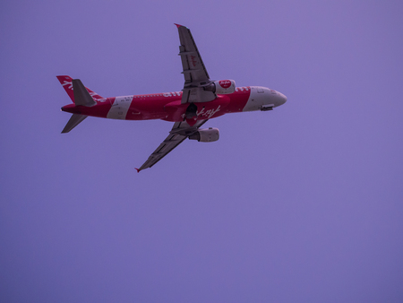 Phuket, Thailand - May 25, 2016 : The moment of Thai Air Asia airplane folding its landing gear after take off for awhile, the plane is still pitching up toward sky for reaching flight path altitude.