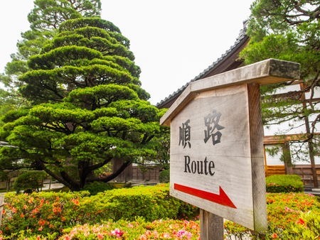 The wooden sign shows the direction of the route with the red sign and its also written in japanese with the same meaning of the direction, just for guiding the tourists to the walkway.