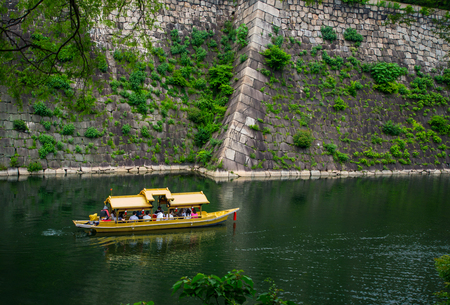 The sight seeing japanese vintage style boat is moving around the Osaka castles wall where it is surrounding by the lake and the green nature.