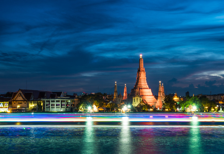 Wat Arun or Temple of Dawn is the most famous landmark of Bangkok, Thailand. it is also printed on 10 baht coin. The temple is shining with lighting behind the rainbow lines from transport vehicles. Stock Photo