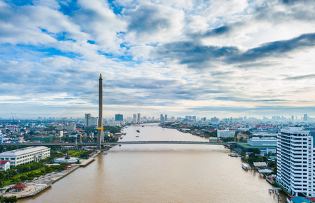 Morning sun rises in Bangkok city with the view of great rope bridge in the city named Rama VIII brdige. The high angle view is taken from drone. Stock Photo