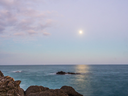 뒤에 파도의 움직임과 함께 전경에서 바위의 선택적 초점. 달은 또한 바다의 수평선 위에 빛난다.