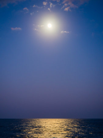An amazing phenomenon of supermoon. The moonlight is so strong its bright enough to give the light path along the sea in the blue ocean of Pacific. The best thing to look at while traveling in the sea Stock fotó