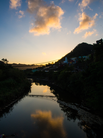 The last moment of the sun. The beautiful sky behind the mountain is reflected to the water. The rope bridge is really nice looking from here. The location is Shifen shopping area in Taiwan. Stock Photo