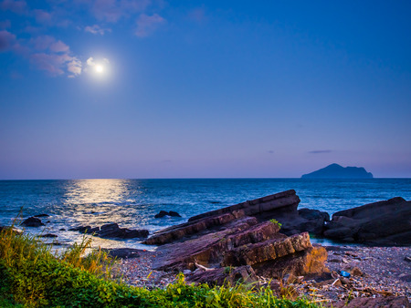 The beauty moment of moon nature and sea. The great supermoon is shining above the Pacific ocean. The moonlight is so strong, the light reflect to the sea in long and wide way toward the rocky shore. Stock Photo