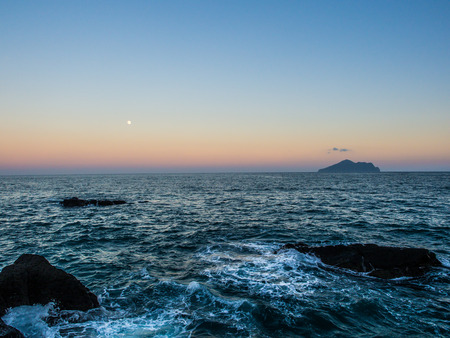 The moon and island is showed very far away above the colorful horizon from the sunset light. The texture of sea wave hitting the rock also nice in foreground. The nature of beach is always beauty.