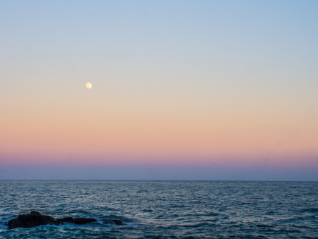 The moon is shining above the gradient color of sunset sky. The color is shown from yellow to pink to purple down to the horizontal line of the blue sea.