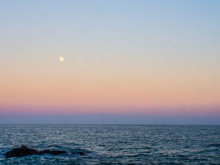 달은 일몰 하늘의 그라디언트 색상 위에 빛난다. 색상은 노란색에서 분홍색, 보라색, 푸른 바다의 수평선까지 표시됩니다.