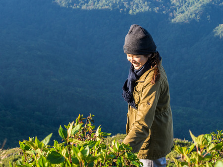 The wonderful smile of an asian girl bove the mountains valley of Doi Phu Wae in Nan province, Thailand. The moment of human with the love of a green nature is totally nice to catch.