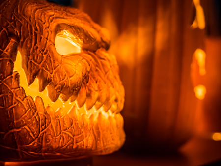 The selective focus on the face of an orange scary pumpkin with the growing light inside of Halloween decoration night at the end of October.