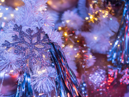 The selective focus on the snowflake decoration of  christmas tree. This make the background blur and become colorful heart shape bokeh behind. Merry Christmas. Foto de archivo