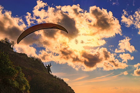 Paraglider flying over a beach in BaliIndonesia Stock Photo