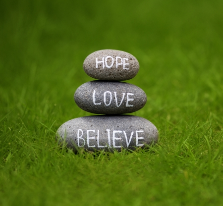 Believe, hope and love rock in the grass  photo