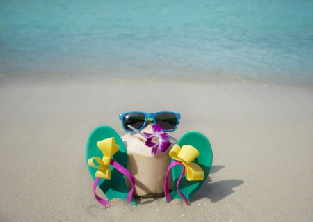 Coconut with drinking straw on a beach photo