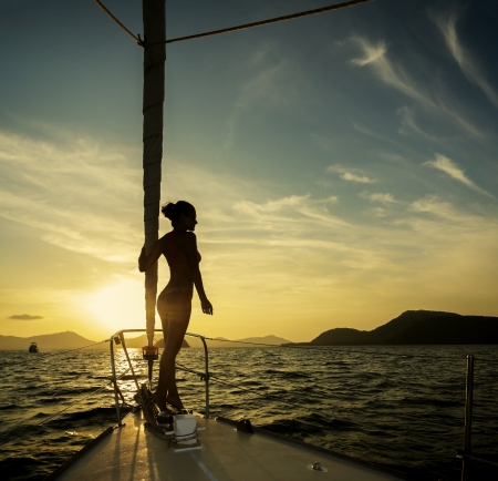 girl standing on a yacht at sunset photo