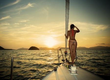 夕焼けのヨットの上に立っている女の子 写真素材