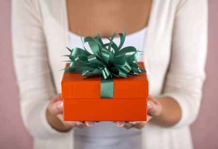 greeting season: Hands holding beautiful gift box, female giving gift, Christmas holidays and greeting season concept, shallow dof Stock Photo