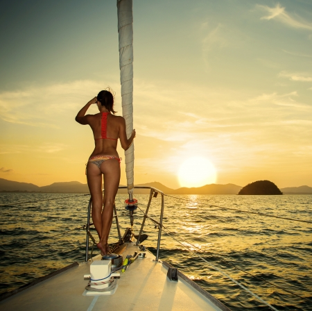 日の出セーリング ヨットの弓で若い女性のシルエット 写真素材