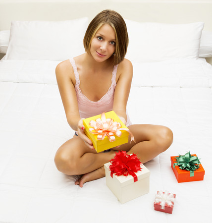 finds: Woman in underwear finds a surprise in bed, white background Stock Photo