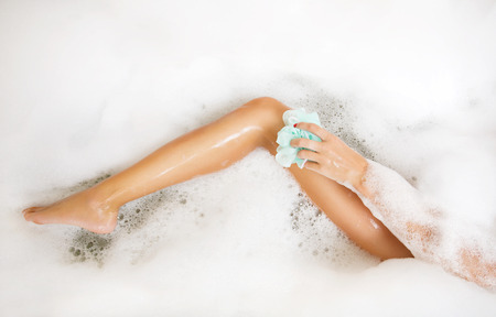 Woman in bath washing leg in bathtub with a lot of bubble bath foam  Leg of beautiful young woman in bath in bathroom