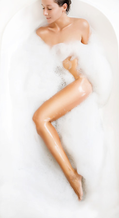 bulles de savon: belle jeune femme brune prend un bain de bulles