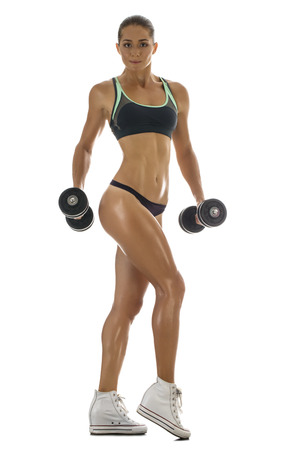 Body of slim female in activewear doing exercise with dumbbells photo