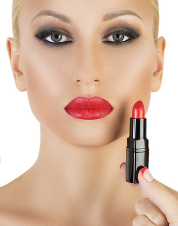 applying lipstick: attractive woman portrait on white background applying lipstick