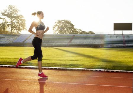 選手は朝日の出トレーニング マラソンとフィットネスのために実行しています。アクティブなライフ スタイルの健康的なラテン系の女性運動