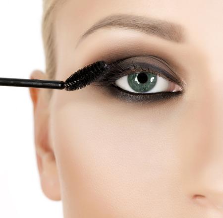 eyelashes: Woman applying mascara on her long eyelashes
