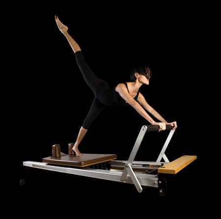 reformer: Pilates reformer workout exercises woman at gym indoor
