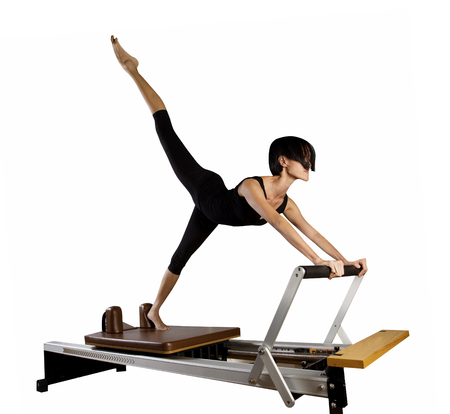 Pilates reformer workout exercises woman at gym indoor