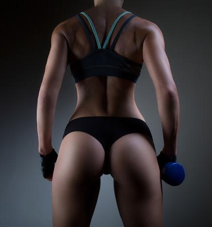 セクシーなフィットネスお尻のクローズ アップ。フィットネス体に黒の背景の一部です。女性のスポーツは完璧なお尻。フィットネス女性がスタジ