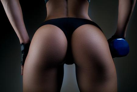 セクシーなフィットネス臀部のクローズ アップ。フィットネス体に黒の背景の一部です。女性のスポーツは完璧な臀部。フィットネス女性がスタジ 写真素材