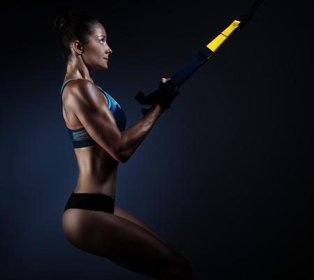 暗い背景に trx で運動を行う筋肉美人 写真素材
