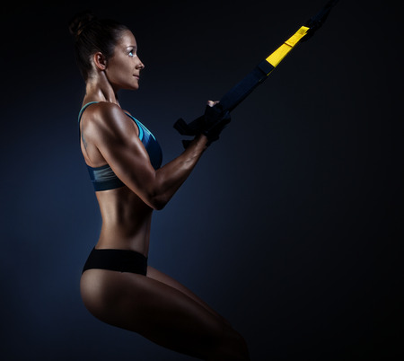 Beautiful muscular woman doing exercise with trx on a dark background