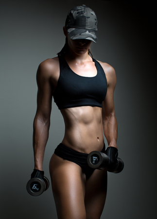 日焼けした体に強いフィットネス女性ボディービルダーは、ダンベルを持ち上げる筋肉をポンプします。