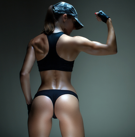 完璧なフォーム。フィットネス女性の魅力的な熱いスポーティーな体のスタジオ ショットをトリミング 写真素材