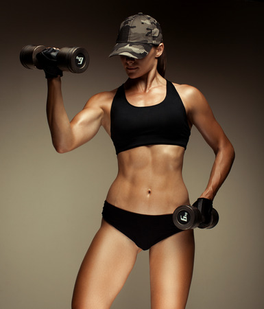 tanned body: Strong fitness woman bodybuilder with tanned body pumps up the muscles lifting dumbbells.