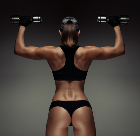 Strong fitness woman bodybuilder with tanned body pumps up the muscles lifting dumbbells.