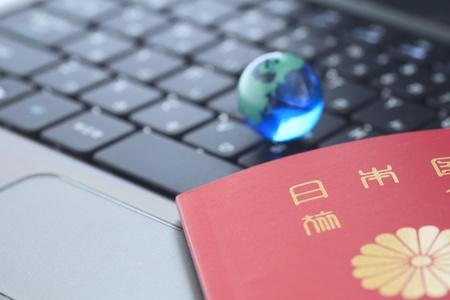 Glass globe and a passport  over keyboard Stock Photo - 11392374