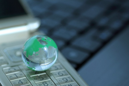 Glass globe over cellphone Stock Photo - 11392378