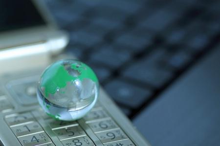 Glass globe over cellphone Stock Photo - 11392378